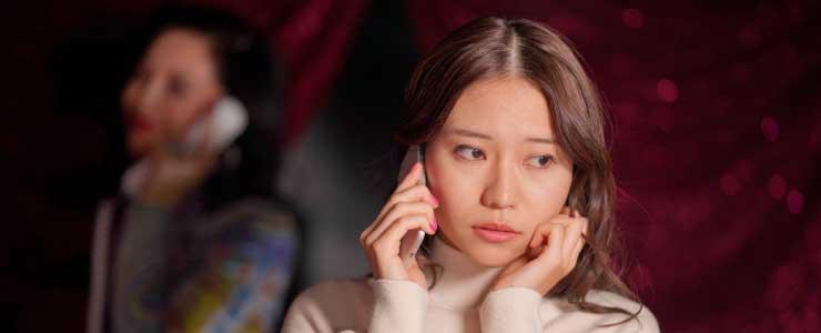 電話占い師と悩む女性